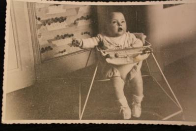 Une photo d'antan d'un tout petit dans son trotteur en ferraille